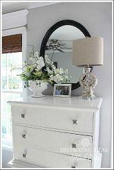 Witte comode van Ikea met antieke knoppen en romantische decoratiestukken om de lege muur tussen de ramen op te vullen. #myikeabedroom