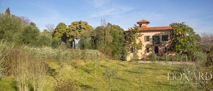 Originally built in the 1700s on top of a hill, this luxury villa is surrounded by tall trees and olive trees.