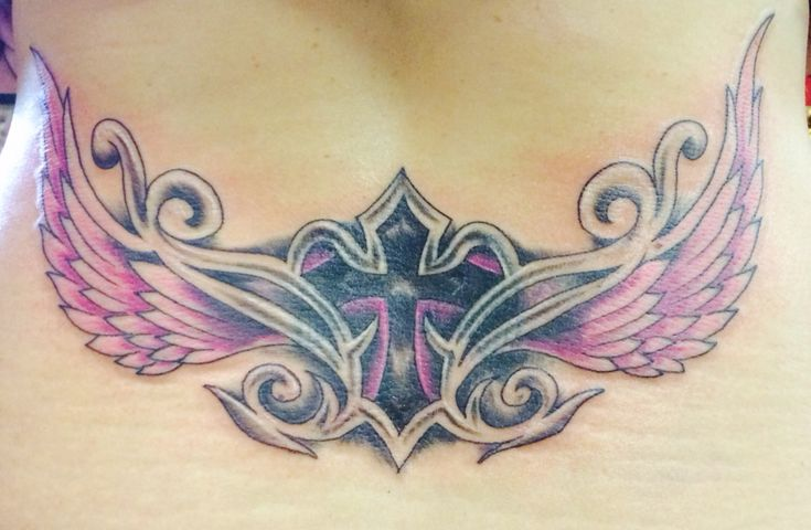 Lower back tattoo. Cross and wings