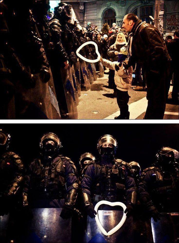 Un bambino romeno tiene nelle mani un palloncino a forma di cuore per la Polizia antisommossa durante le proteste contro le misure di austerità a Bucarest.