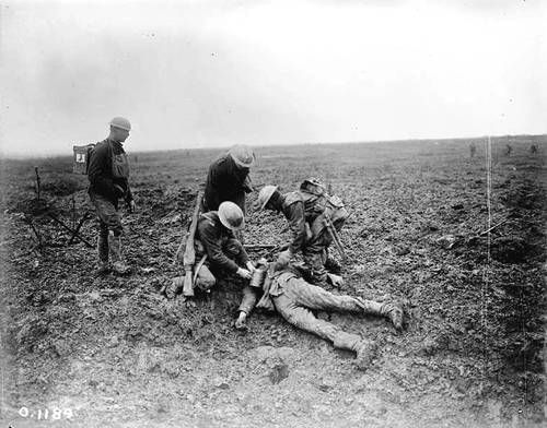 Canadian soldiers inspect the body of a dead German soldier at the crest of Vimy which they have just taken. April 1917.