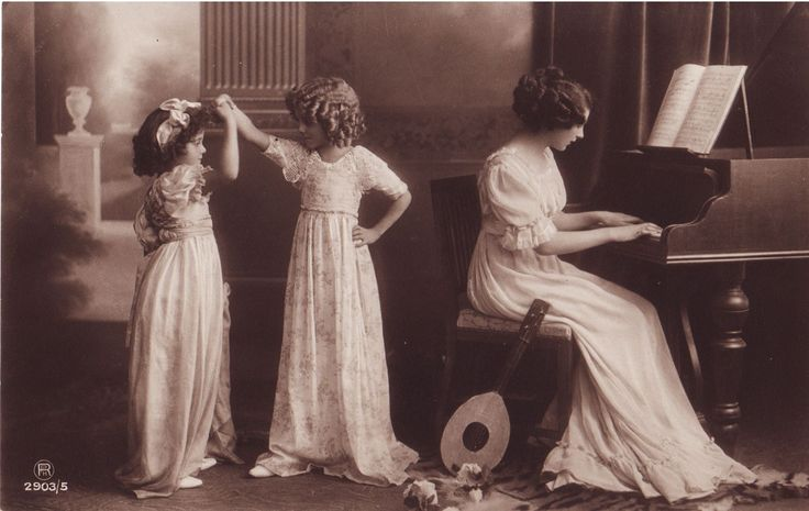 Hanni and Grete Reinwald and an unknown model at piano. Grete and Hanni were enrolled in ballet lessons, so they likely played like this at home in real life.