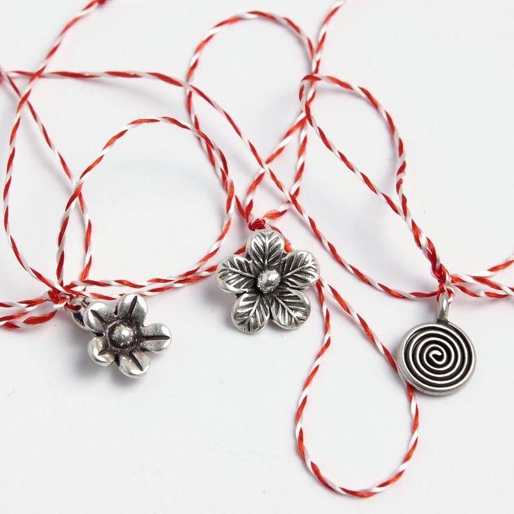 Set de trei mărțișoare-charm din argint. Două dintre mărțișoare sunt în formă de floricele iar al treilea de spirală. Fiecare dintre micuțele pandantive poate fi purtat ulterior ca un charm la mână sau la gât, pe lanț sau șnur. Fiecare mărțișor este ambalat individual într-o punguță cadou, gata pentru a fi oferit.
