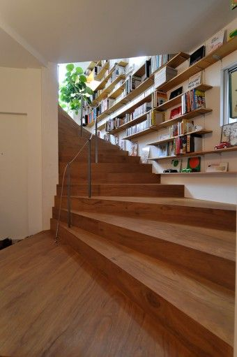 1階から2階へと至る階段。階段脇の壁には本棚がずっと続く。