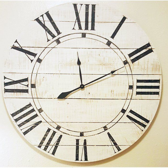This Oversized Farmhouse Wall Clock features a large size face made with horizontal cedar wood slats in a off- white finish, hand painted black Roman numerals in a poster condensed font and an inner accent ring with individual hour marks. It includes a high torque quartz movement, antique-style spade hands and hardware to hang it.