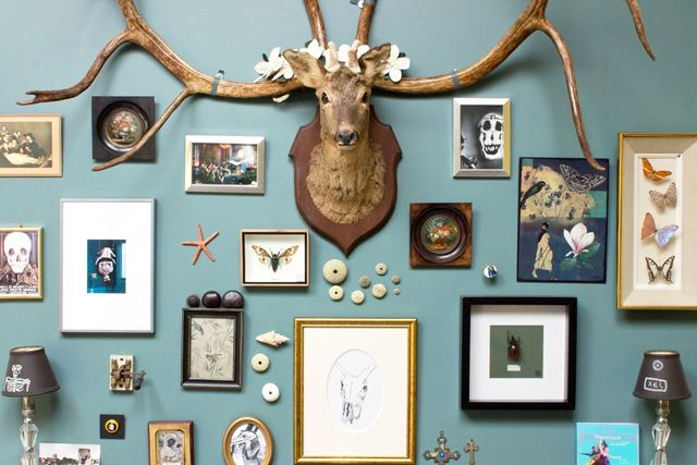 Beautiful blue wall hung with a diverse collection of framed pieces and striking objects.