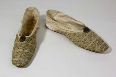 It is believed that these shoes or slippers belonged to Princess Charlotte Augusta of Wales. She was the only child of the Prince of Wales (the future George IV) and Caroline of Brunswick. She was born in 1796 and married Prince Leopold of Saxe-Coburg-Saalfeld in 1816. She died in 1817 as a result of childbirth.
