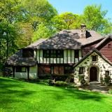 This charming Tudor cottage is located in the Village of Flower Hill and  sits on almost two acres of completely private property. Decorative  stonework, half-timber framing, stone chimney and steep roof   line create the classic Tudor appeal.