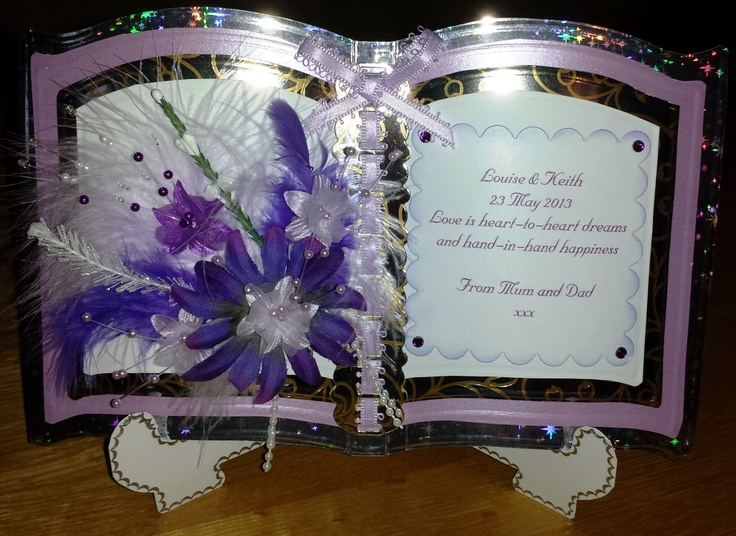 "Four layer bookatrix card. Bottom layer silver holographic, next layer light purple pearlescent, next layer silver mirror with gold foil, top layer white. Ribbon slider down centre cut from silver mirror gold foiled card and lilac fancy-edged ribbon woven through and bow tied at top. Left ""page"" has an assortment of feathers, flowers and pearls. Right-hand page has personalised message on white scalloped square edged with lilac and purple gems added."