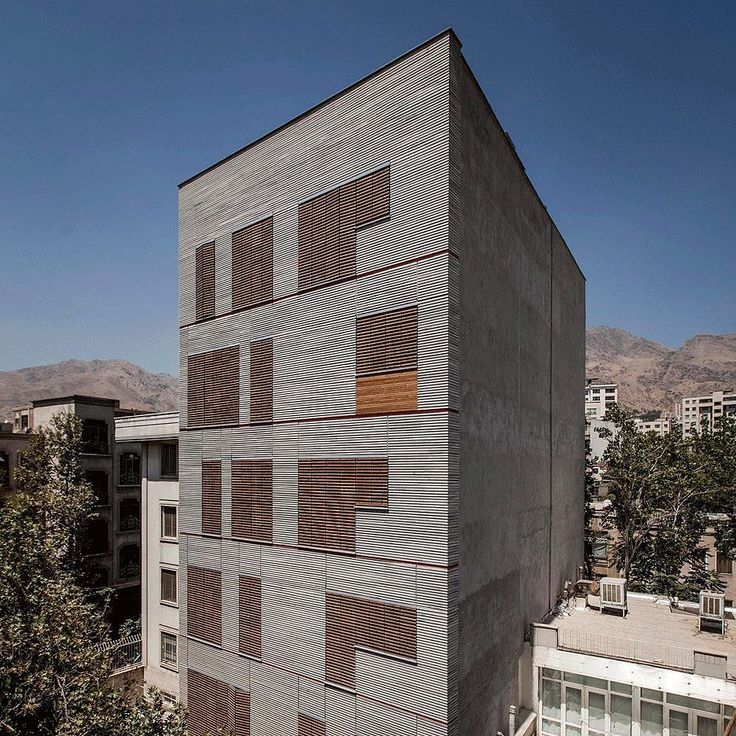 Slatted timber shutters provide privacy and shade for this Tehran apartment block by local firm Ayeneh Office and line up with its ridged granite facade. Photograph is by Farshid Nasrabadi. See our recent Instagram posts for more housing in Tehran or visit http://ift.tt/1T39a7S #architecture #housing #Tehran by dezeen