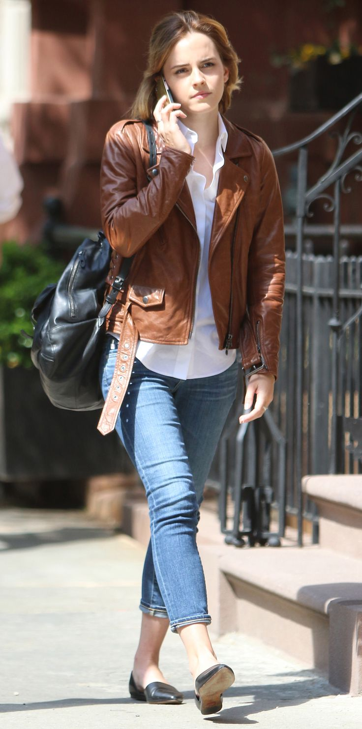 In a rare street-style sighting, Emma Watson was snapped in an on-point off-duty outfit—she dressed up a pair of cropped skinnies with a white button-down, a brother leather moto jacket, a drawstring backpack, and black d'Orsay flats.