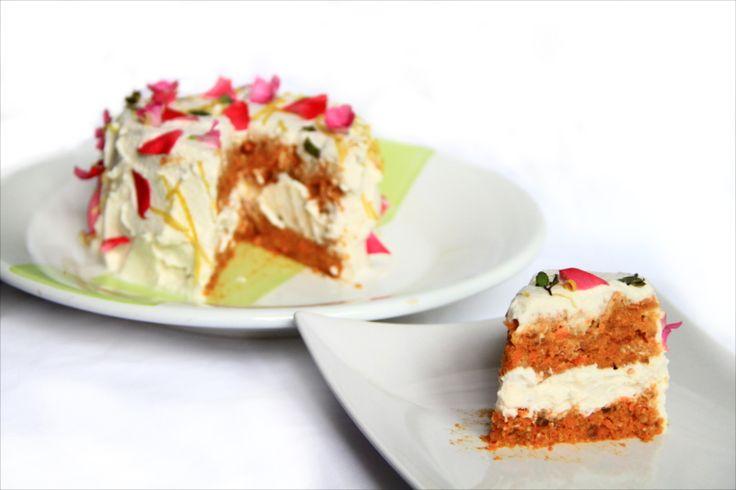 Una torta di carote fantastica, farcita con panna di mandorle e decorata con fiori, scorza di limone e menta fresca.