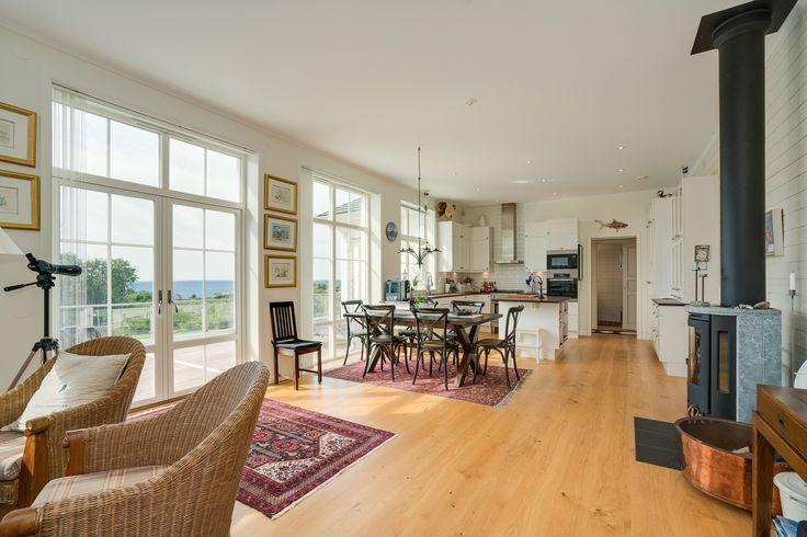Vardagsrummet är öppet och ljust med dubbeldörrar i glas mot altanen. De spröjsade fönstren ger känslan av modern New England, en stil som passar bra här!