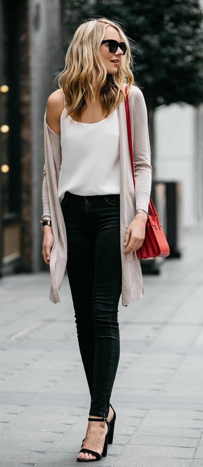 Beige cardigan over white camisole and black jeans.