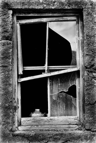 Paraffin lamp by a broken window, Scottish Highlands.