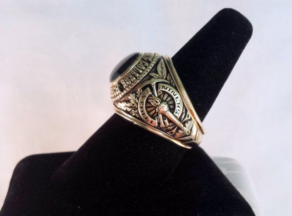 This nice, heavy ring has a large frame--22 mm across--with an approximately 9 carat Natural Black Star Sapphire center stone. The well-made 10k Yellow Gold mount is stamped California State College Long Beach, and dated 1965. Made by John Roberts. Total Weight 25.7 grams. Size