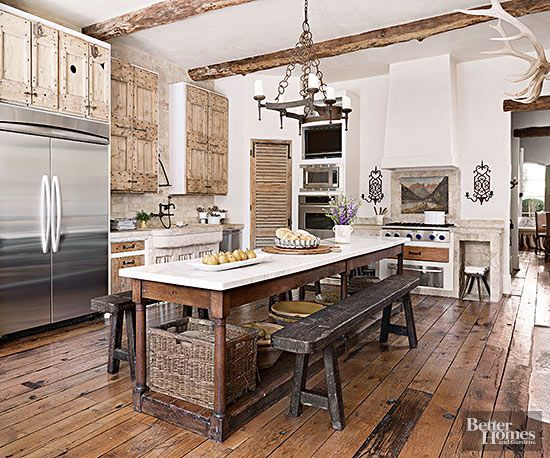 Half timbers, complete with visible bark, make noteworthy ceiling beams in this spacious #kitchen #design, where reclaimed floorboards anchor a blend of aged fittings. The expansive stone-crowned island bears the look of a hand-carved furniture piece, while antique benches contribute period patinas and family-friendly seating.