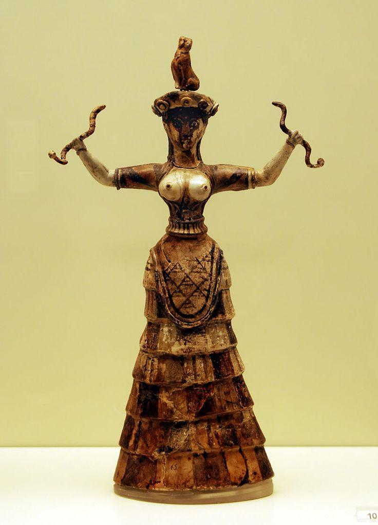"""""""Déesse aux serpents"""" minoenne - Statuette en faïence d'une déesse, ou prêtresse, avec les seins nus et portant de riches vêtements. Sa poitrine découverte permet de supposer qu'il pourrait s'agir d'une déesse de la fertilité. Elle fut découverte par Sir Arthur Evans lors de fouille sur le site de Knossos en Crête - Environ -1600 avant notre ère."""