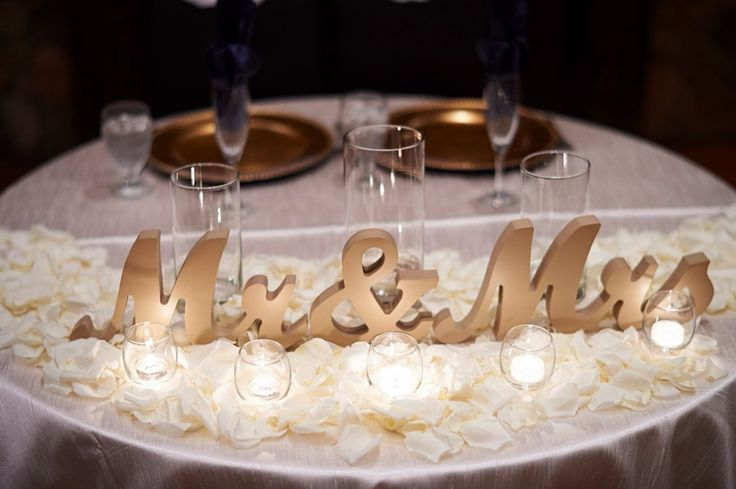 Beautful sweetheart table signs in stunning gold and accented with rose pedals and candle light. This is the most romantic table for the newlyweds that I've ever seen! Perfect for the bride and groom. ♥️ | http://www.ZCreateDesign.com or ZCreateDesign on Etsy