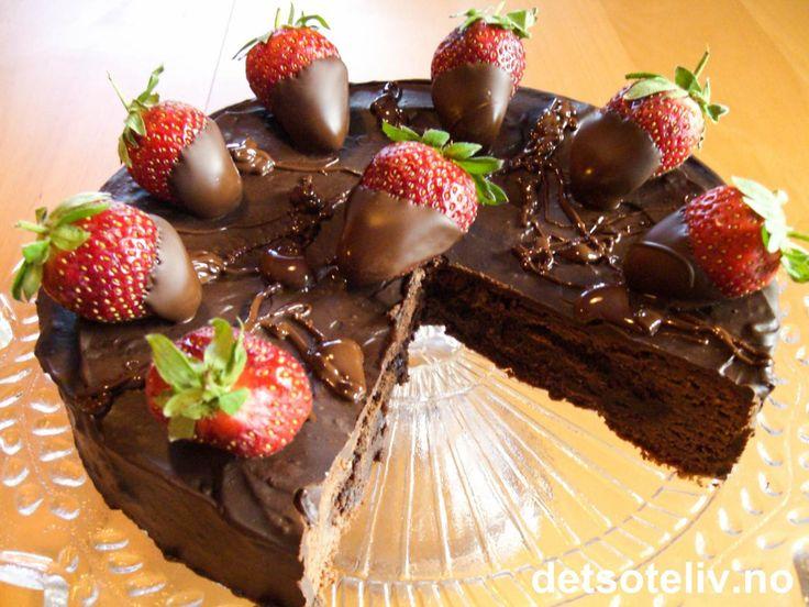 """""""Konfektkake med jordbær"""" er en lekker og forførerisk sjokoladekake som består av en mørk og fuktig kake med intens sjokoladesmak, som er dekket med en fyldig sjokoladeglasur og pyntet med friske, søte jordbær dyppet i mørk sjokolade......."""