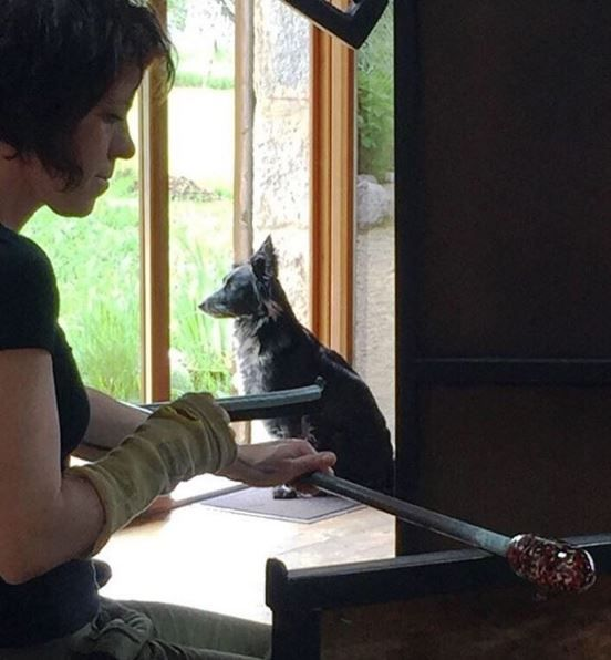 """Vanessa at work in the glass studio, alongside her trusty companion 'Tit Bout (French for """"Little Bit""""). This sweet puppy loves to curl up in the corner for a snooze while the artists work and the ovens hum…but is always ready for a game of fetch when visitors come round."""