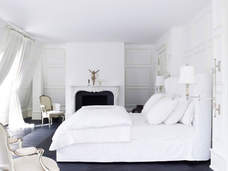 White bedroom features white slipcovered wingback bed dressed in layers and layers of soft white bedding accented with swing-arm sconces and built-in wardrobe cabinets over almost black wood floors.