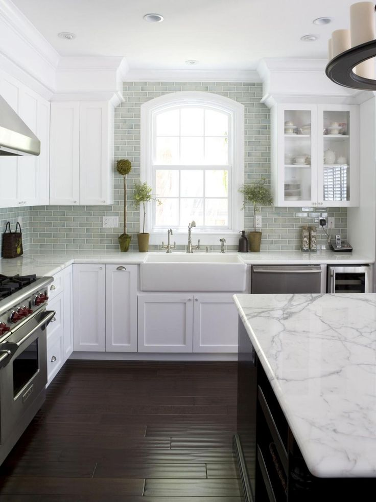 Dream Kitchen white cabinets dark floor and dark island with marble counter  tops and pale blue subway tile