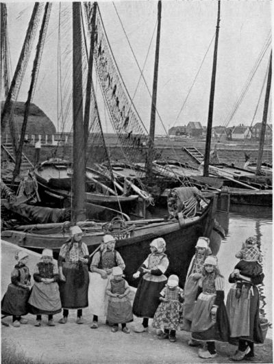 "♥THE HARBOUR OF MARKEN. Girls, wearing a many-coloured costume, are waiting for the tourist. The town is one of the ""show-places"" of Holland."