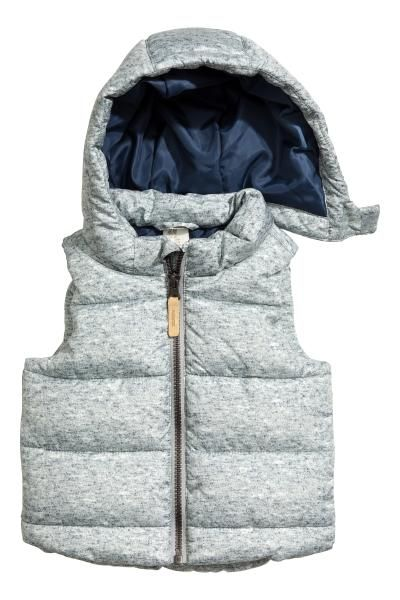 Padded gilet with a detachable, padded hood, stand-up collar and zip down the front. Rounded hem. Lined.