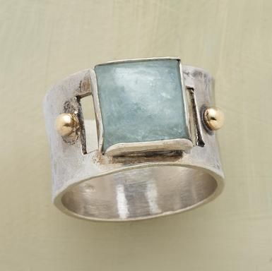 an aquamarine cabochon is framed by hand in sterling silver. The band is hammered sterling sparked with gold granulation beads.