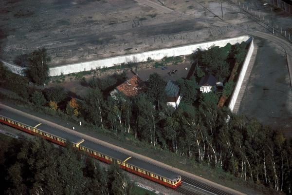 1986, die S-Bahn rollt an der Mauer entlang; dahinter ein kleines Stückchen West-Berlin.