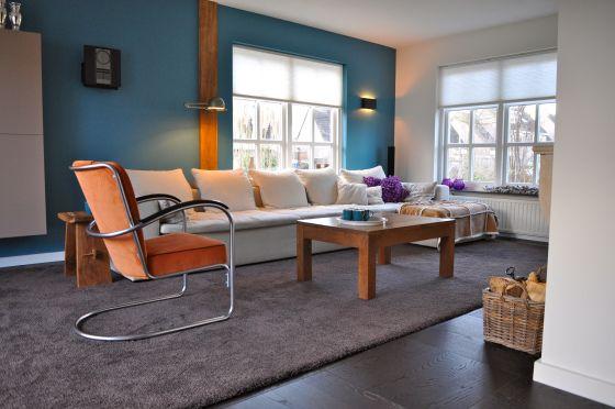 Woonkamer met blauwe muur gispen stoel en witte bank for Interieur schilderen