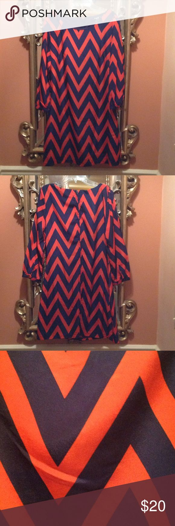 Size 9 Chevron Dress Size 9 Coral and navy blue Chevron dress. It is fully lined with a zipper down the back. It is long sleeved with a button at the wrist. Perfect condition. Dresses