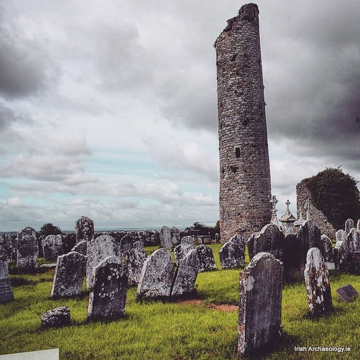 Lichen covered headstones and an 11th century round-tower, Tullaherin, Co Kilkenny