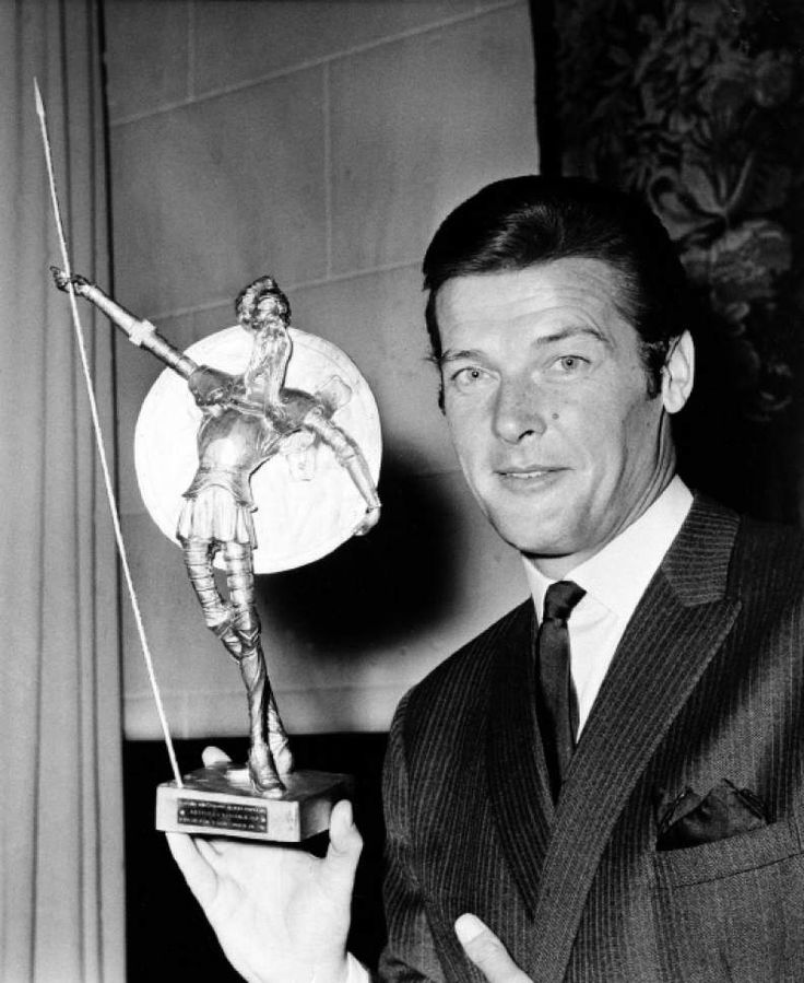 """July 8, 1968: Roger Moore poses with the Don Quixote Award, presented to him at the Spanish Embassy in London. The Spanish equivalent to Hollywood's Oscar, was awarded to him for his role in the British series """"The Saint,"""" one of the most popular shows on Spanish TV."""