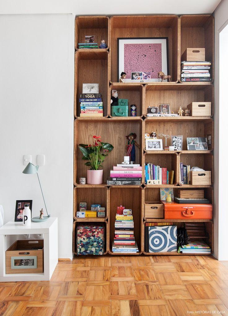 Estante de madeira com desenho interessante é um dos atrativos desse quarto de casal.