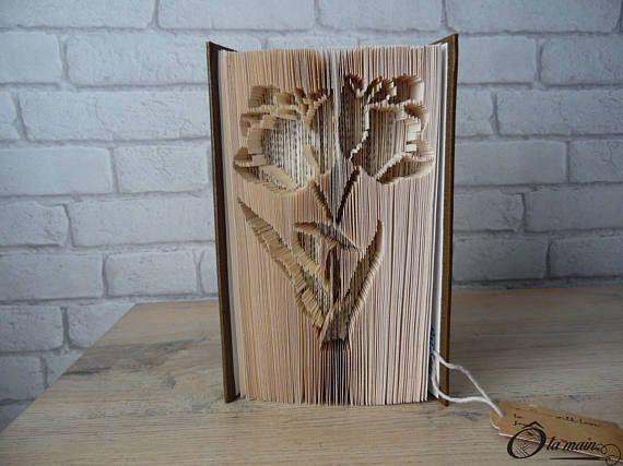 La collection A Livre Ouvert est une série de livres doccasion transformés en objets de décoration via plusieurs techniques (découpage, pliage ou décou-pliage). Chaque page est découpée et/ou pliée à la main pour donner vie à un motif.  Le modèle Bouquet de Fleurs est un livre découpé et plié pour représenter 2 fleurs entrelacées. Le livre possède une magnifique couverture vert et or. VENDU SEUL