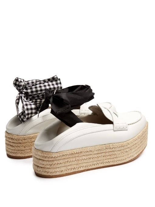 Trimmed with the signature contrasting black and gingham ribbon ankle ties, these white leather espadrille loafers capture Miu Miu's eye-catching aesthetic perfectly. They're crafted with a rounded toe and set atop a beige braided-jute flatform. Wear the heels folded up or down, and watch them bring a cool, contemporary tone to tailored separates.