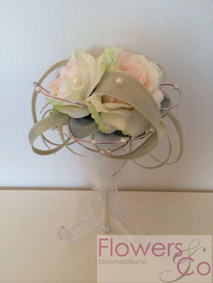 Romantisch bruidsboeket met rozen, tilandsia prachtig bewerkt met ijzerdraad en parels. Steel gedeeltelijk afgewerkt met (nep) bont. Voor meer info: www.flowersenco.nl