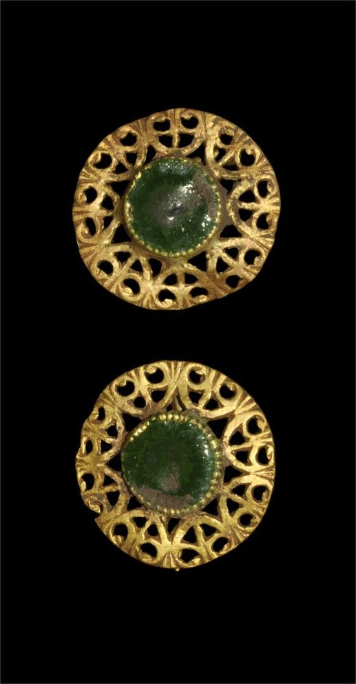 ROMAN OPENWORK DISC EARRINGS Circa 3rd-4th century AD. A pair of earrings comprising a green glass disc set en cloison within an openwork pattern of D-shaped panels with scrolled outer edges; on the reverse, double-loop attachment wires. Gold and glass