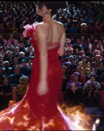 El mayor atractivo del vestido, el efecto fuego, se consigue gracias a los efectos por ordenador. Sin embargo, las llamas ya recorren todo el vestido gracias al inmenso trabajo de plisado y reconstrucción de la falda. De pie, la falda podría parecer recta pero los pliegues permiten el vuelo de campana una vez que está en movimiento.