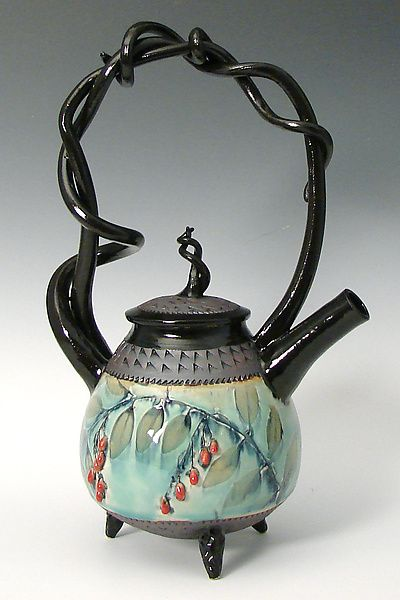 """Basket Handled Teapot with Red Berries"" Ceramic Teapot ~ Created by Suzanne Crane ~ Crane's signature piece, the wheel thrown teapot with twining hand pulled stoneware handles now has ripe red berries to give it a little extra pop. Stoneware feet are textured with the same churchkey pattern as found on the lid and at the rim & base of the teapot body."