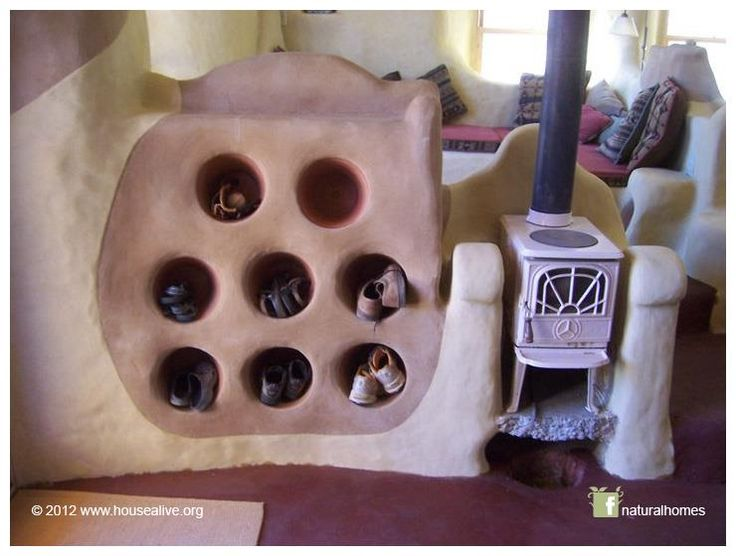 This is some creative thinking by Coenraad Rogmans of House Alive [www.housealive.org] near Jacksonville, OR, USA. The shoe tidy is made from clay pots set in cob which doubles up as a thermal mass beside the wood stove. So not only will it radiate heat keeping the room warm but it keeps your shoes warm too. Cute idea!