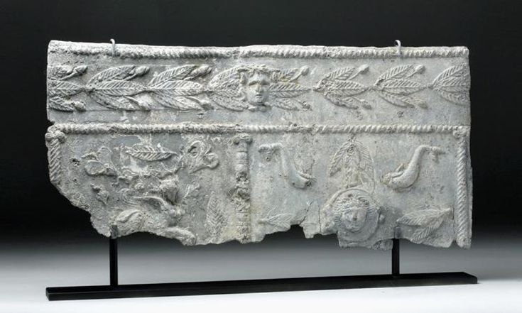 Roman Empire, ca. 2nd to 3rd centuries CE. A very heavy lead, rectangular sarcophagus panel, with extensive cast relief decoration, the upper frieze featuring a relief band of laurel leaf vines sprouting berries or flower buds inspired by the actual garlands and flowers used to decorate tombs and altars, with a frontal visage of Medusa emerging from the center, all framed by two finely delineated borders of twisted cable molding or ropework.