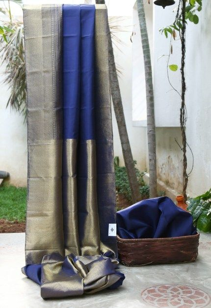 CLASSIC NAVY BLUE HAS INTRICATELY WOVEN GOLD BORDER AND PALLU GIVING THE SAREE TRADITIONAL FINISH. THE HEAVY GOLD BLOUSE ADDS TO THE BEAUTY OF THE SAREE.