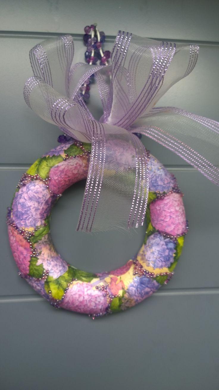 Ovikranssi servetit styrox-pohjalle, sisustusneuloilla pieniä helmiä, ripustimeen helmiä ja kukkakorista rusetti
