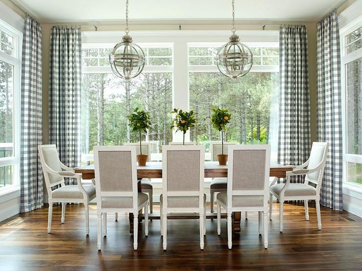 Chic dining room features a trestle dining table lined with heather gray square back French dining chairs illuminated by Restoration Hardware Victorian Hotel Pendants surrounded by windows dressed in blue gingham curtains.