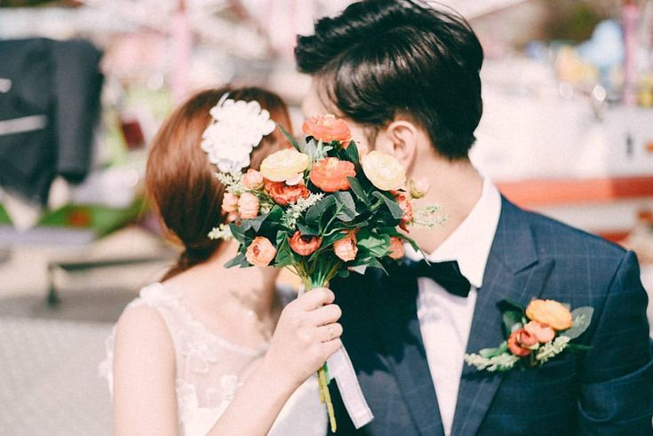 Couple, Front facing, Half body shot, Bouquet, kissing, Hiding face,  Casual or formal outfit,  Fun shot