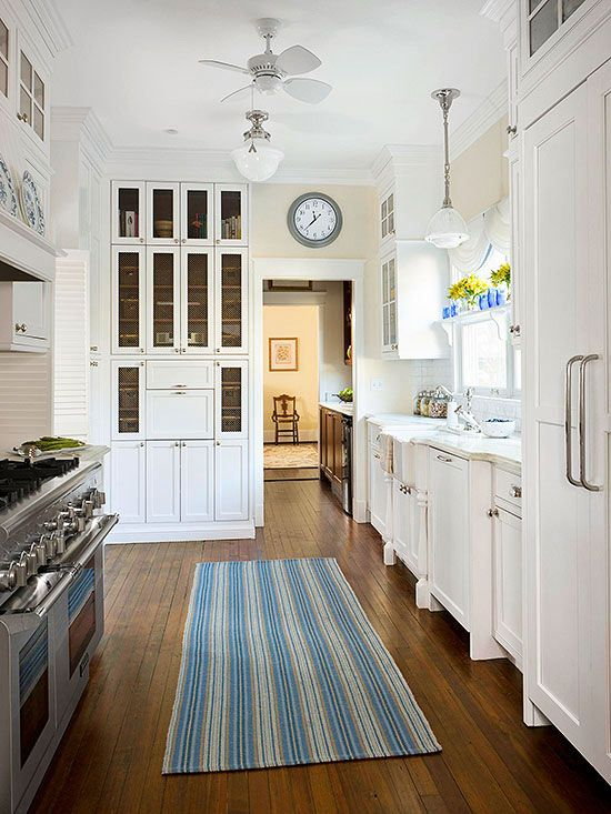 Maximize vertical storage in a long and narrow galley kitchen with cabinets that reach all the way to the ceiling. Use the additional cabinet space to store items you don't use everyday like platters and seasonal dishes. Glass-front doors keep the tall cabinets from overwhelming the space. Kitchen Dimensions: 16' x 10'
