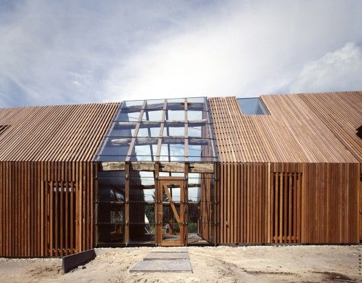By cladding the roof and elevations with a continuous skin of horizontal timber laths, the façades simultaneously have the appearance of being open, semi-transparent and closed.